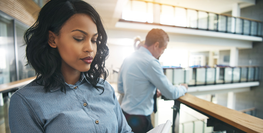 young-black-woman-thinking-over-notepad-in-office